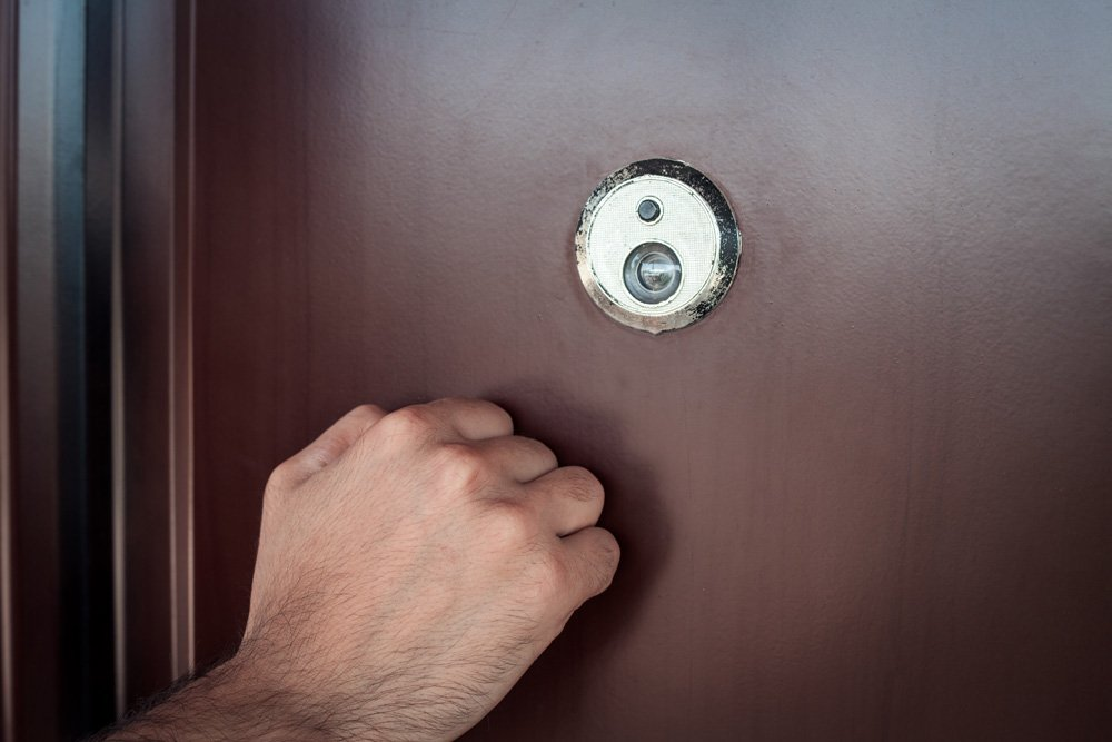 person knocking on door with peephole