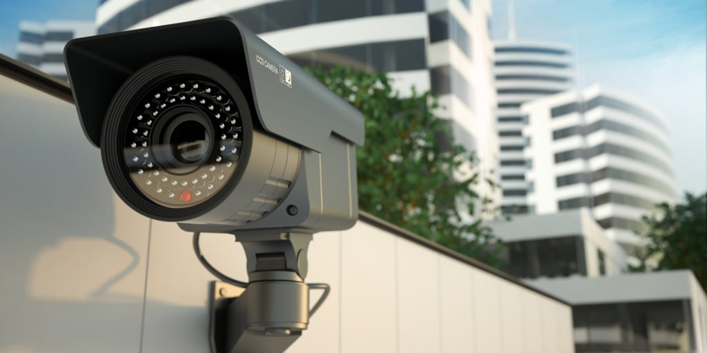 security camera on corner of building with business buildings in background