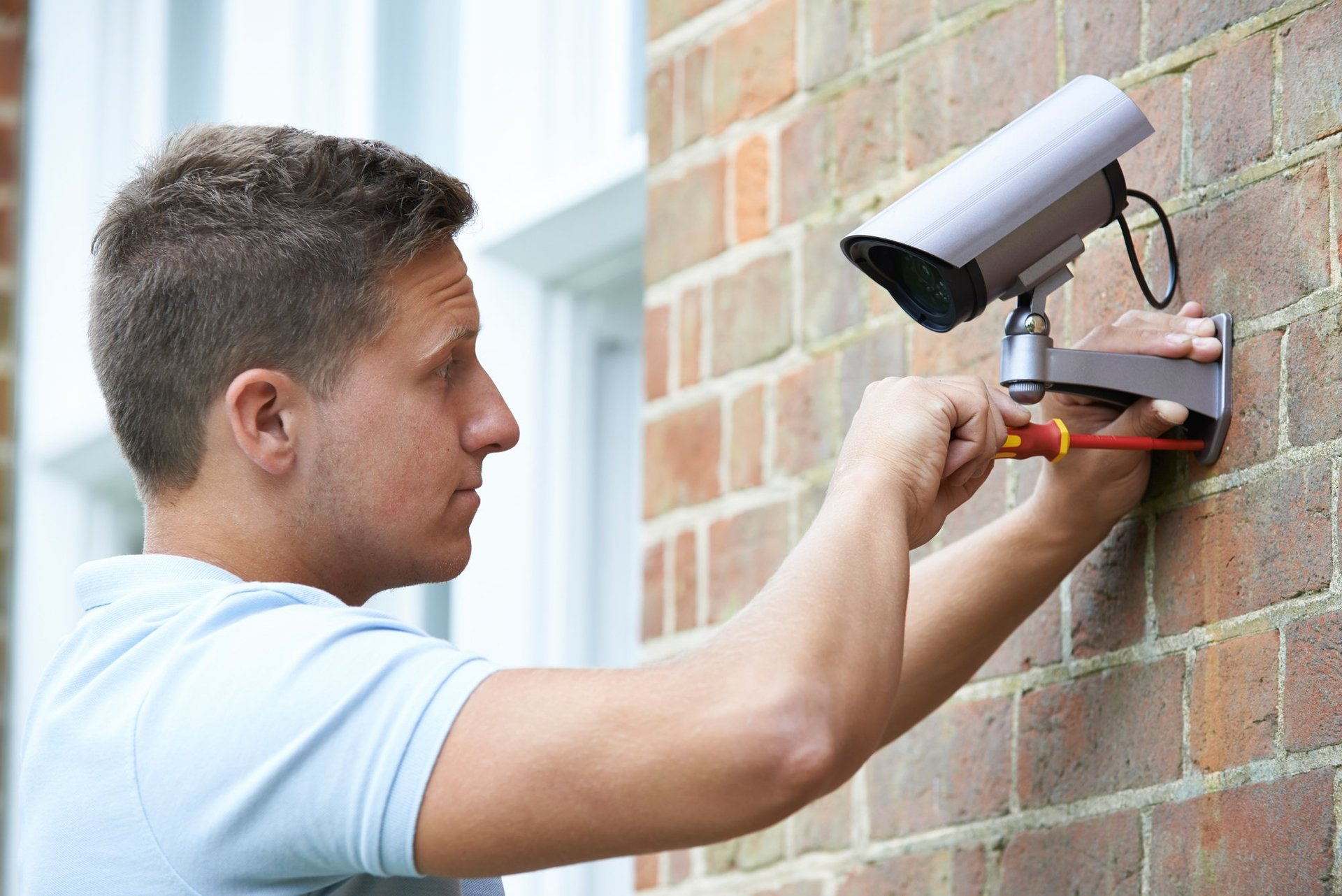 man installing security camera